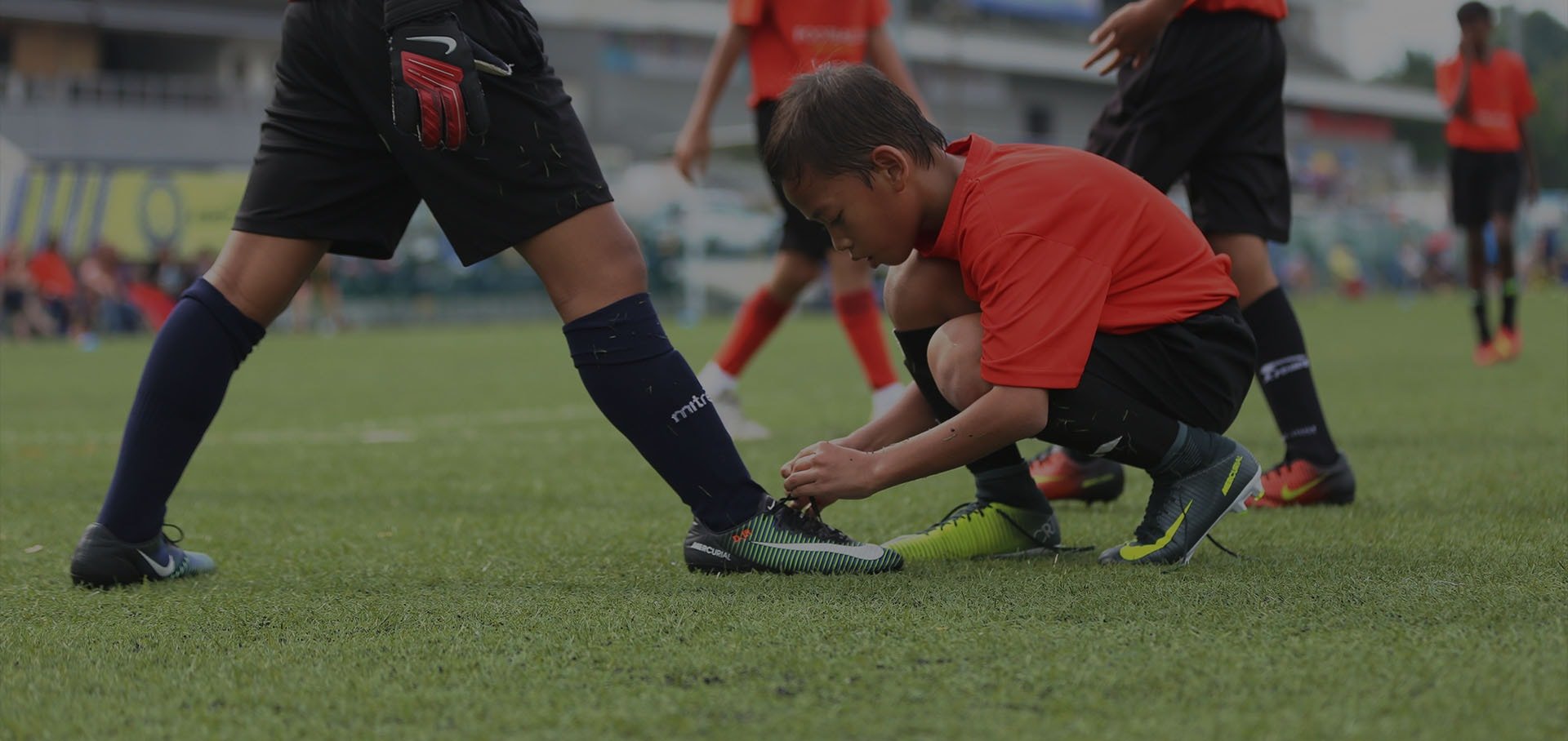 1 kid tying his teammate's shoelaces