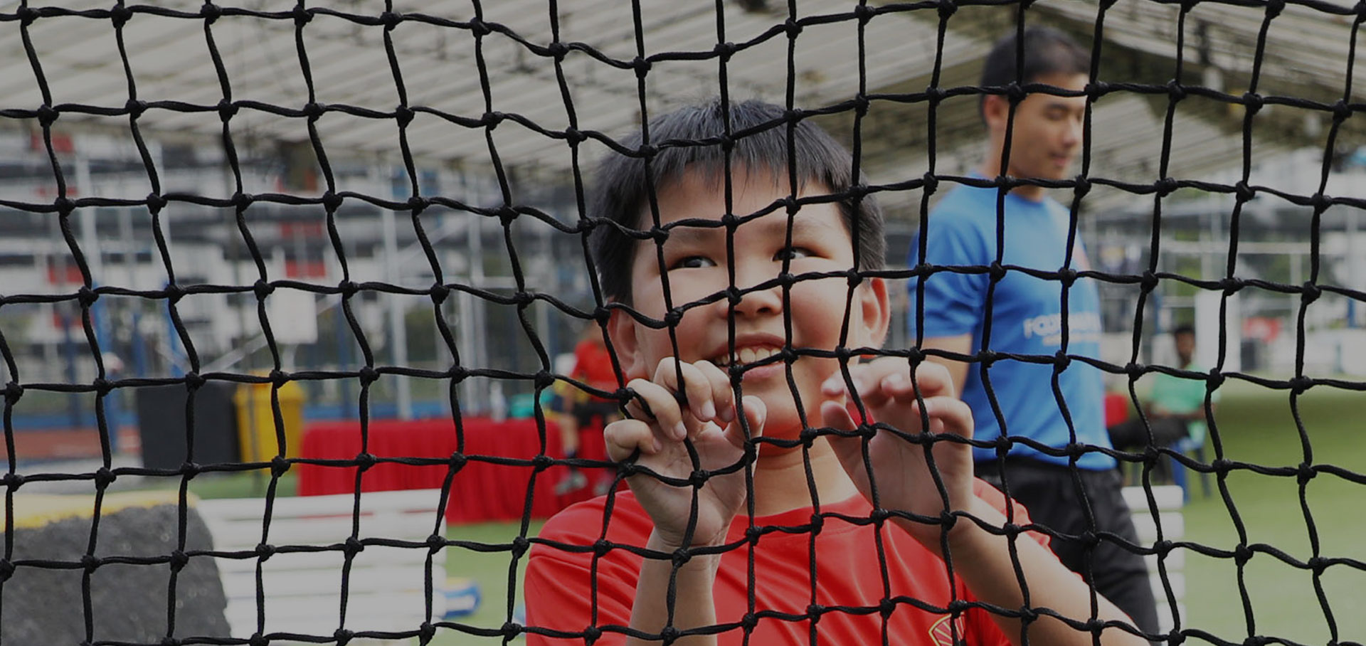 kid and coach behind a net